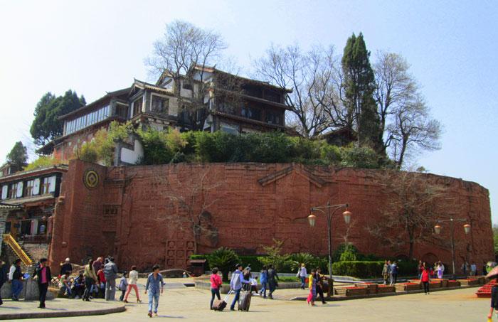 Gerbang masuk Ancient City Lijiang ditandai dengan tembok dan plakat World Heritage Site