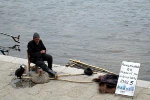 Pria tua menunggu turis yang mau berfoto dengan burung di pinggir Sungai Li.