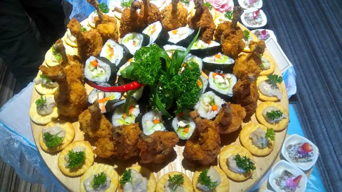 Chicken drum stick, sushi roll, and tuna crackers.